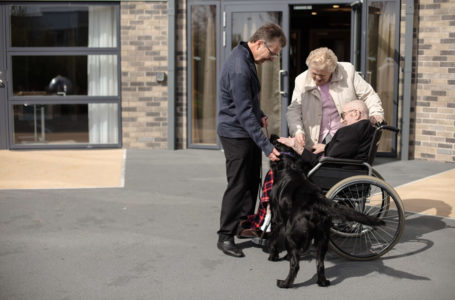 Residents and loved ones with their pet dog outside Casa di Lusso Dementia Nursing Home Bridgwater Somerset