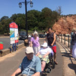 Residents and staff walking along Sidmouth beach