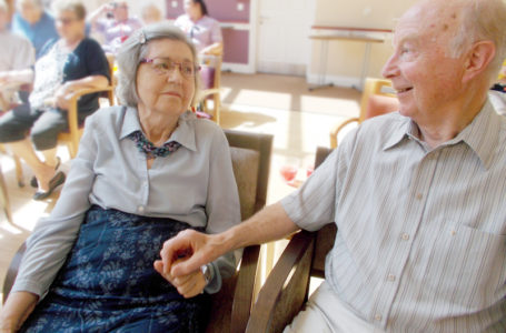 La Fontana Care home Martock resident and loved one holding hands during musical entertainment