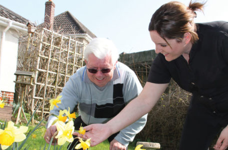 Notaro Care Assistant with service user looking at the daffodils in the garden