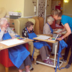 Susannah working with the residents on their butterfly pastel art
