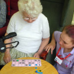 Resident with care assistant playing bingo
