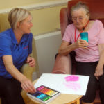 Pauline, activities coordinator helping resident with her butterfly artwork