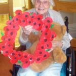 Resident with their homemade poppy memorial wreath