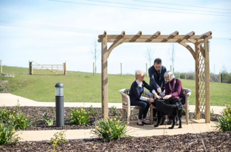 Resident and loved ones with their pet dog sat in the gardens at Casa di Lusso Care Home Bridgwater Somerset