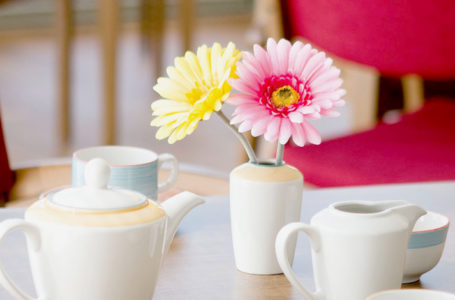 Close up image of tea set and faux flowers in Notaro care home dining room