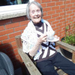 Resident sat in the garden with a cup of tea