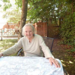 Resident sat in the garden smiling for the camere