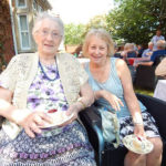 Resident and relative in the garden with their scones