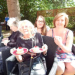 Resident and relatives in the garden, smiling to the camera with their scones