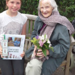 Resident with Curry Rivel pupil presenting her Life Story book and flowers