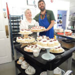 Chef, Janet with kitchen assistant next to a trolley full of Janet's homemade scones and cupcakes