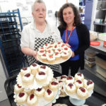 Janet holding a tray of her homemade cupcakes, with Cedar Lodge staff member