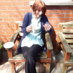 staff member in the garden with a cup of tea