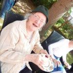 Resident sat in the garden enjoying a scone