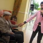 Emilio Santoro-Elvis impersonator singing to resident