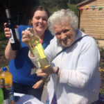 Activities Coordinator, Louise with resident's loved one holding their raffle prizes