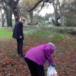 Resident picking fallen leaves with Activities assistant, Caroline