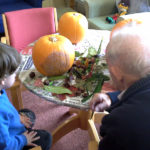 residents and Little Pips children decorating pumpkins