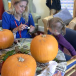 Activities assistant, Caroline, with Little Pips child gluing leaves to pumpkins