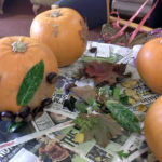 Pumpkins decorated with autumn leaves and conkers