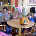 Little pips children with Immacolata House resident showing their decorated ribbon dragonfly, butterfly and finished pumpkin
