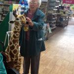 Resident petting a tall giraffe toy at the garden centre
