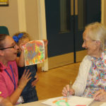 One of the children showing her painting to resident, Georgie