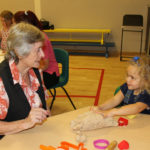 Pam and one of the children getting creative with the playdough