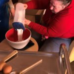 Cedar Lodge resident pouring sugar into cake mix