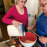 Cedar Lodge resident pouring flour into cake mix