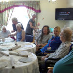Residents and staff with Mary Kembery starting their clay project