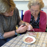 Mary Kembery supporting resident painting clay leaf tiles