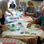 Mary with residents and staff, making leaf prints on paper