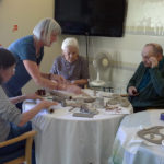 Mary supporting residents with making clay cakes