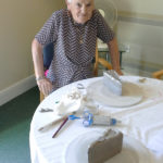 Resident with her finished slice of cake made from clay