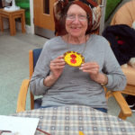 resident with her finished painted clay cake