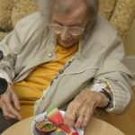 Clarence Park resident tasting and choosing what fruits to have in their cake