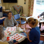Residents and staff making pumpkin paintings with apple stamps