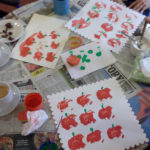 Finished pumpkin paintings using apple stamps