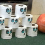 Halloween bowling with a ball and toilet paper with drawn on spooky faces