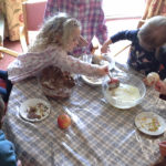 Little pips children and residents decorating apples in chocolate