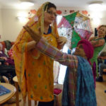 Michele Beleca - Activity Coordinator dressed in colouful indian robes posing with dancer