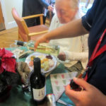 Immacolata House nurse pouring wine for resident and her loved ones