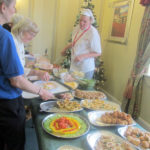Immacolata House residents and loved ones at buffet lunch table