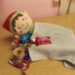 Elf in bed feeling sick after eating too many chocolates