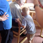 Boy from Little Pips Nursery cuddling resident at Immacolata House Dementia Nursing Home Langport