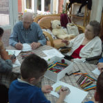 King Ina School pupils colouring in St Patrick's Day pictures with the residents