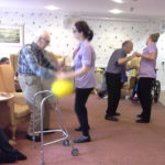 Staff and residents dancing together to Chris Clarke's live music