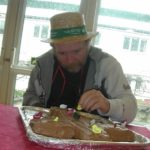 Clarence Park resident decorating the Easter cake whilst wearing a hat for brain tumour research